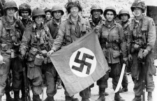 American paratrooper James Flanagan (2nd Platoon, C Co, 1-502nd PIR), among the first to make successful landings on the continent, holds a Nazi flag captured in a village assault. Marmion Farm at Ravenoville, Utah Beach, France. 6 June 1944
