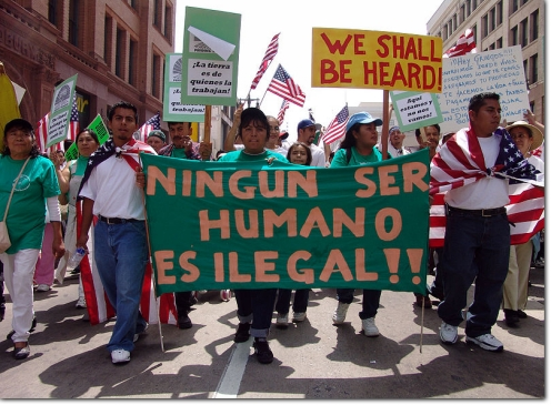 "Members of the South Central Farm attending the immigrant rights march for amnesty in downtown Los Angeles California on May Day, 2006. The banner, in Spanish, reads ""No human being is illegal"". (Photo credit: Jonathan McIntosh)"